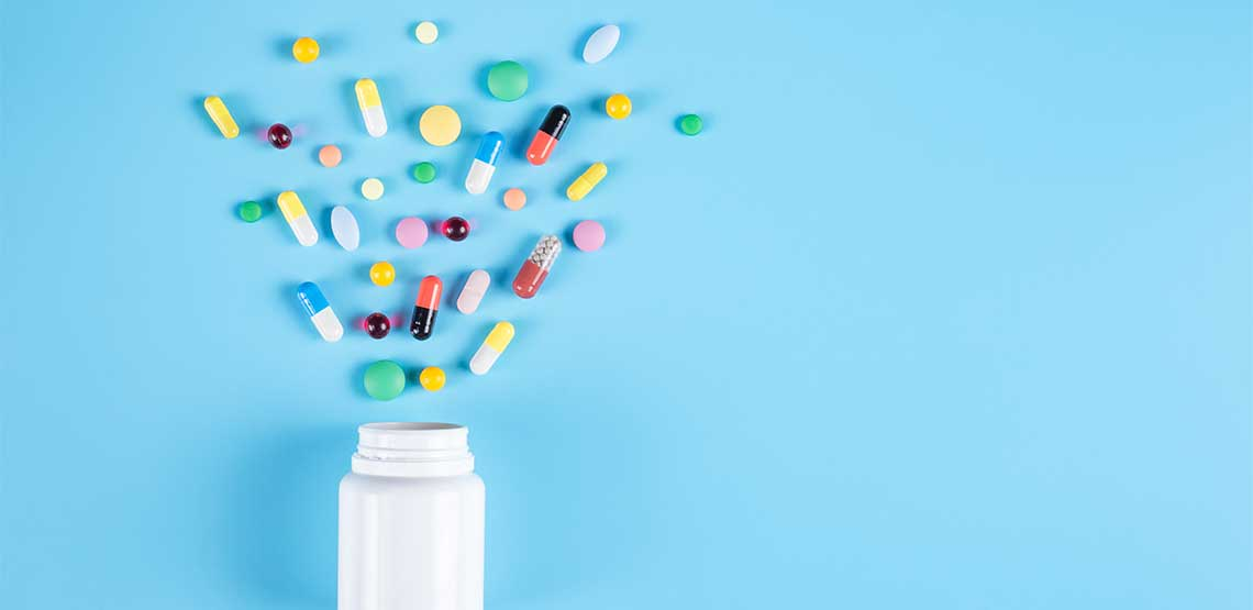 A pill bottle with pills spilling out onto a blue background