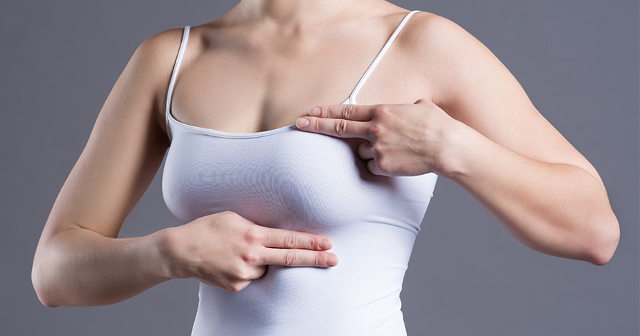 Woman performing breast exam