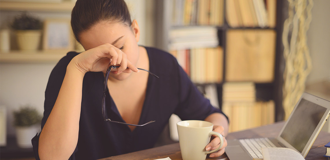 Woman sitting at desk with head on face, in pain