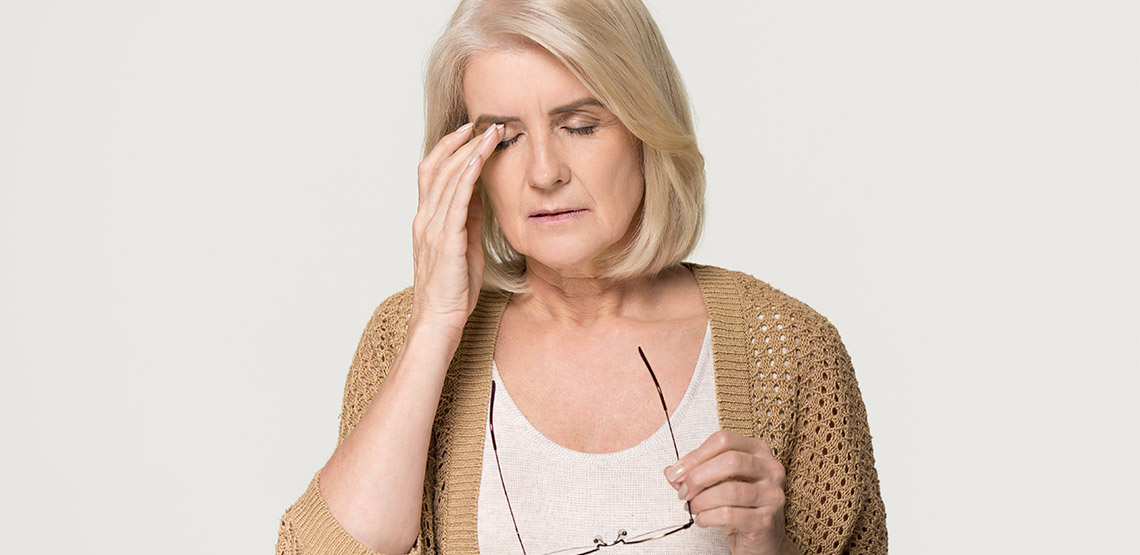 Woman with hand on head in pain