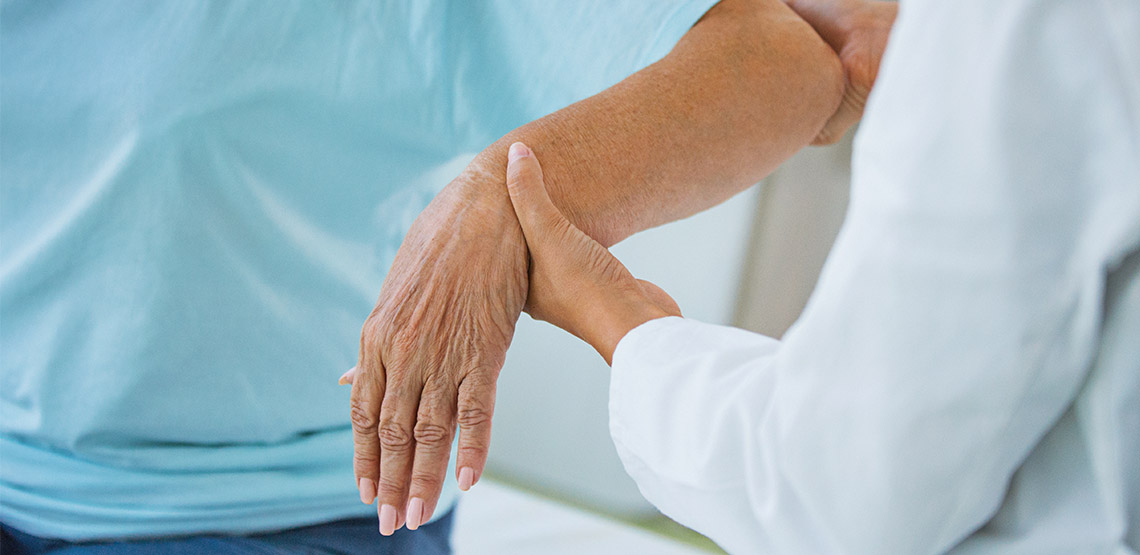 Older woman having arm looked at by physician