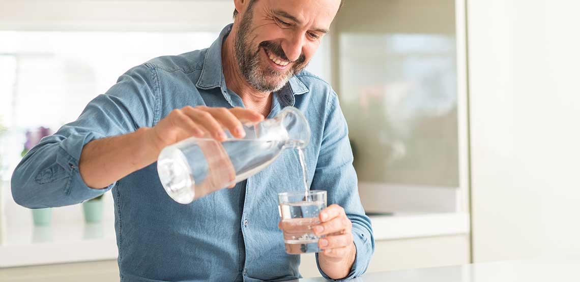 A man pouring himself a glass of water