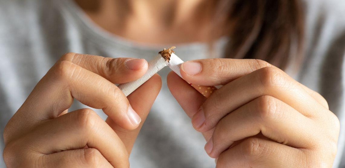 person breaking a cigarette