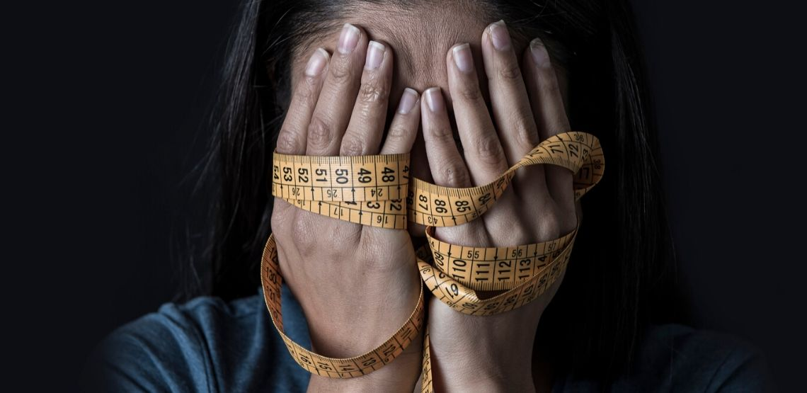 frustrated woman holding a measuring tape