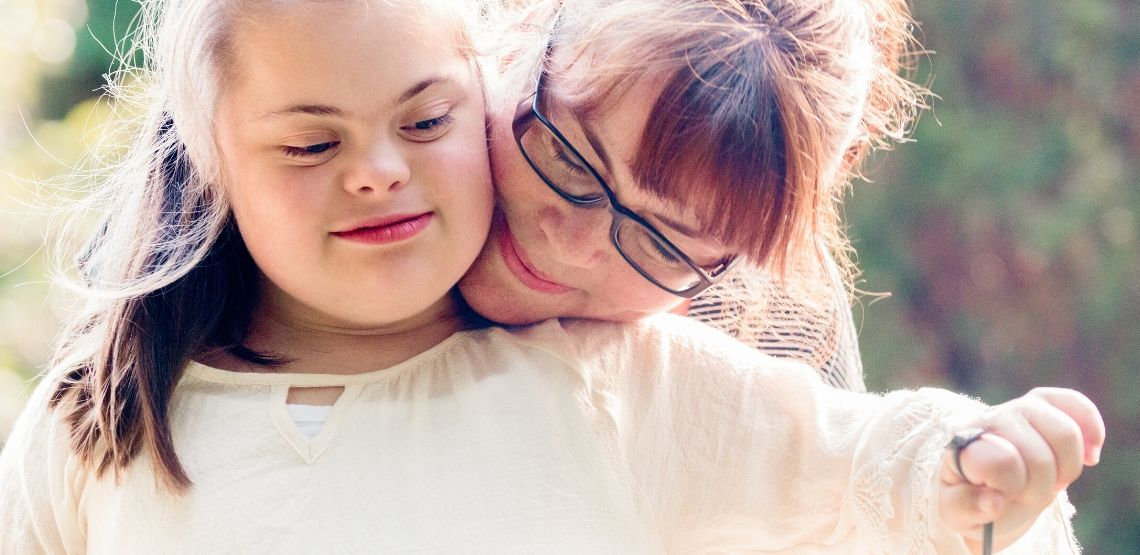 A mother hugging her daughter who has austism.