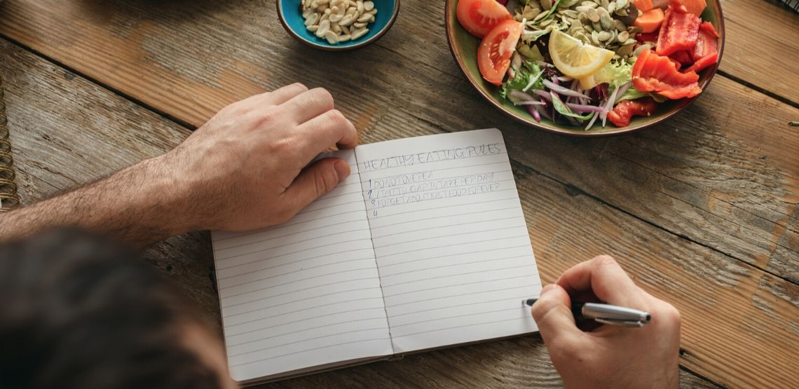a person writing their goals for healthy weight loss in a journal