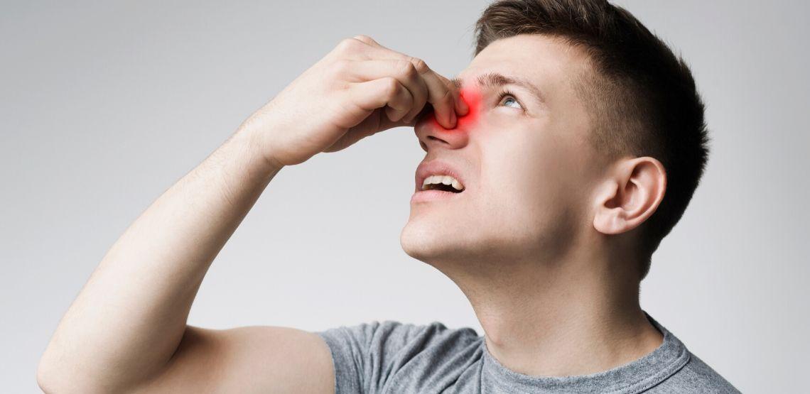 Someone experiencing nasal polyps symptoms.