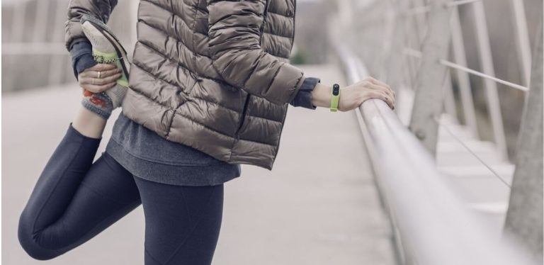 a woman stretching after exercising in cold weather (running)