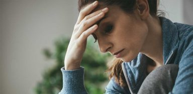 a woman with anxiety feeling overwhelmed, holding her head in her hands