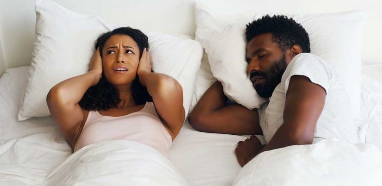 a frustrated woman being kept up by her partner's snoring