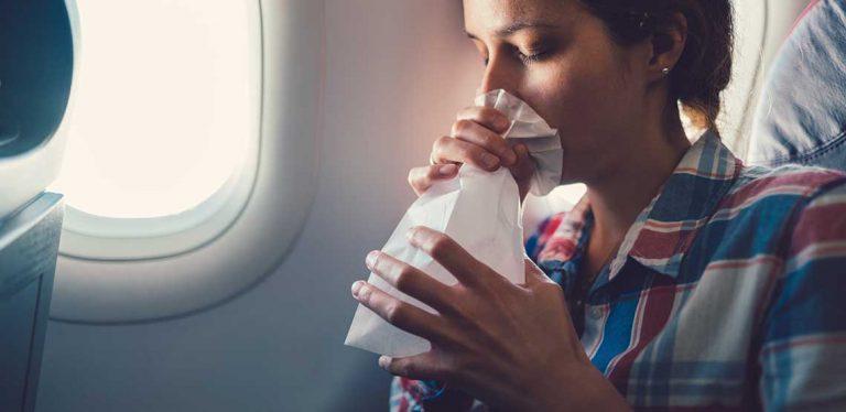 a woman feeling nauseous on a plane