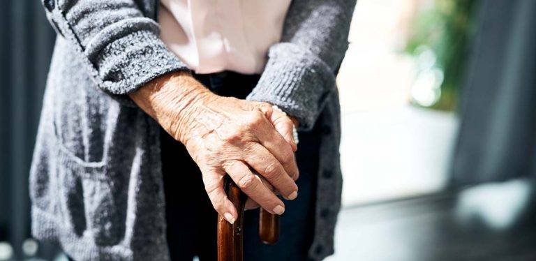 An older person holding a cane.