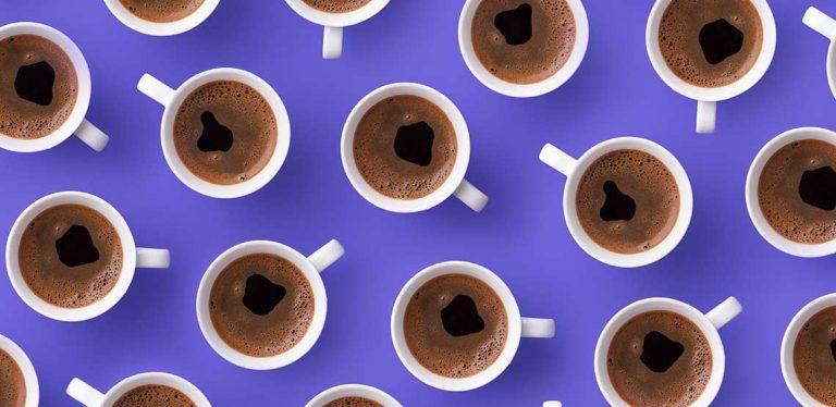 A pattern of coffee mugs on a purple background