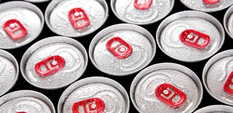 Several drink cans aligned together covered in water droplets