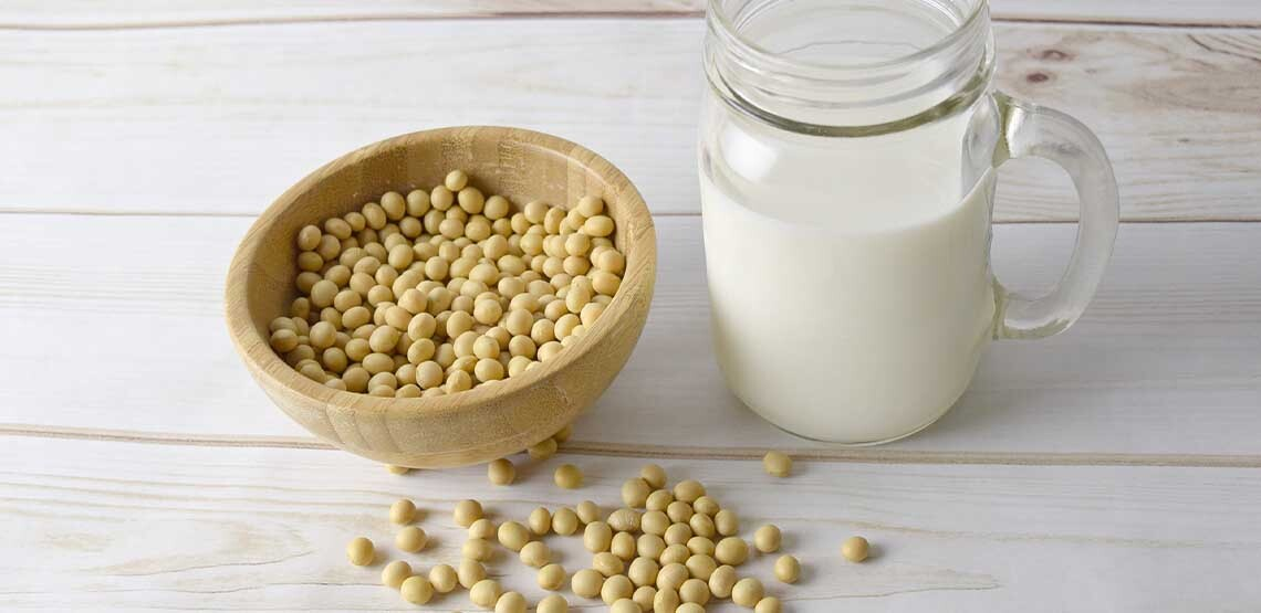 A bowl of yellow soybeans placed next to a glass of soy milk