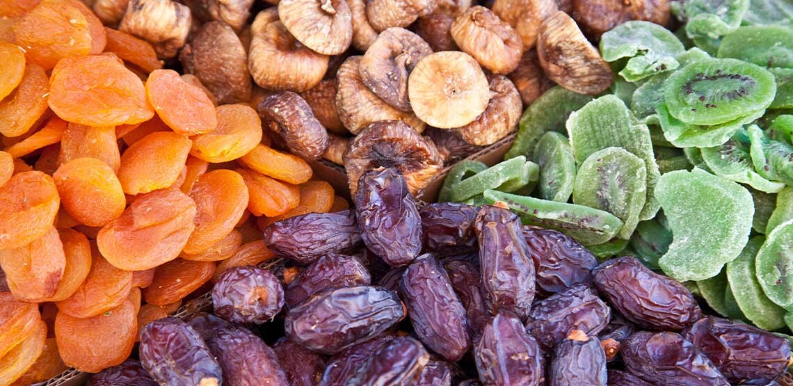 A photo of four types of died fruits. Starting at the top, dried bananas, died kiwis, dried dates, and dried apricots.