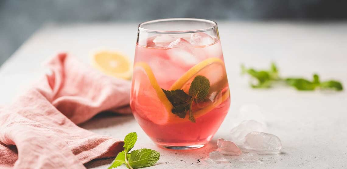A wine glass full of a pink mixed drink with lemon slices and mint leaves. Some ice, lemon slices, mint leaves and a hand towel are scattered on the table around it.